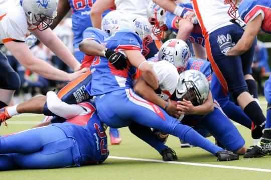 QB Philip Garcia (Nr. 12, Rostock Griffins) im Team-Tackle der Bears
